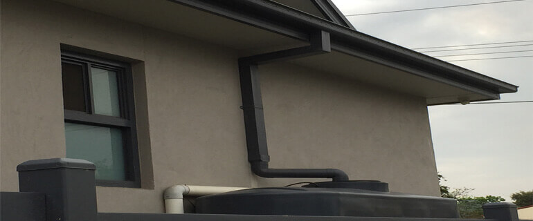 Slotted Quad Gutter & Rectangular Downpipe Flowing Into Rainwater Tank.